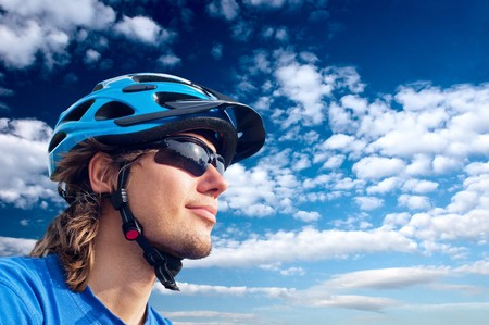 portrait of a young bicyclist in helmet and glasses on a sky background Stock Photo - 7920159