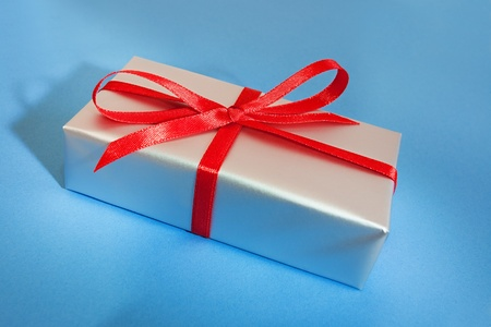 silver gift box with red ribbon on the blue background Standard-Bild