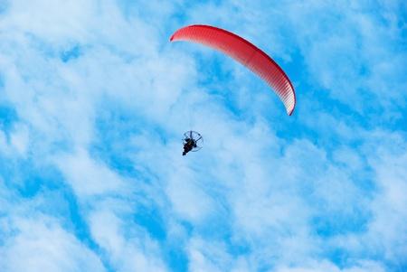 paragliding pilot on the sky background