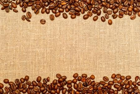 granos de cafe: granos de caf� en el backgruond de arpillera con espacio de copia