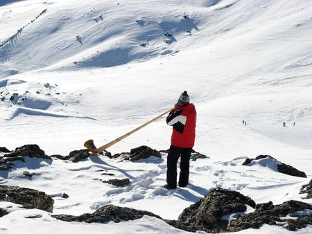 middleages: Man playing alp horn in the snowy mountains