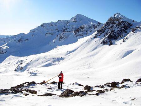 alphorn: Man playing alpenhorn in mountains near Scuol, Switzerland