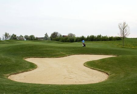 Sand trap (bunker) on the golf course photo