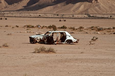Abandoned car wreck in the desert photo