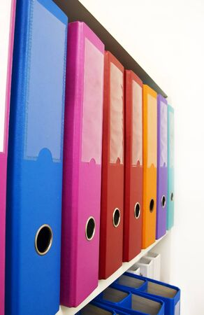 Colorful office folders on the bookshelf photo