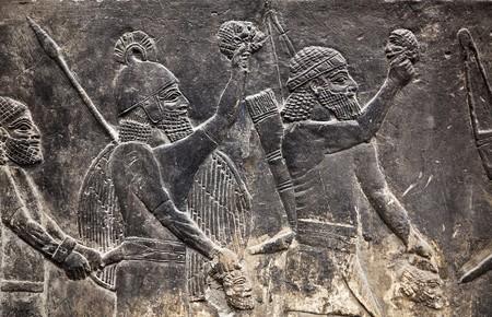 Tallas de la antigua muralla Asiria (guerreros con armas)  Foto de archivo