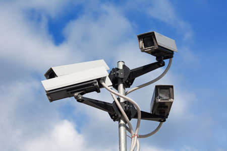 Surveillance cameras against blue sky Stock Photo - 8157375