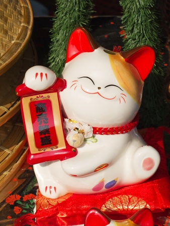 maneki neko: Traditional chinese porcelain cat with golden and red decoration