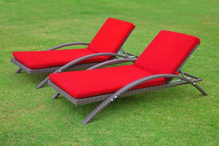 Two empty beach chairs on the grass photo