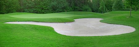 sand trap on the green grass of the golf course photo