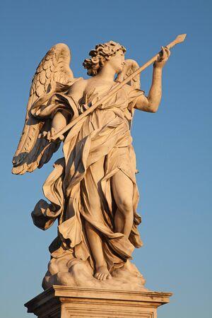 Angel with spear lit by sunset sun, Ponte SantAngelo bridge, Rome photo