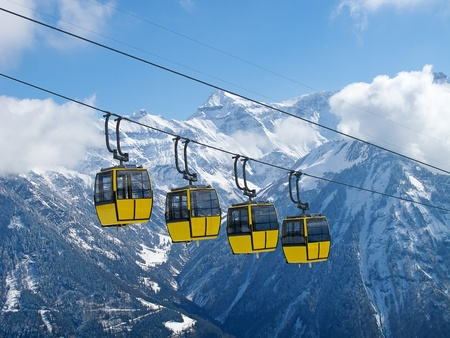 ski track: Group of bright yellow cable car cabines in swiss alps