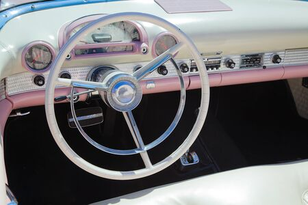 retro styled classic american car interior with white and pink leather upholstery and matching dashboard photo