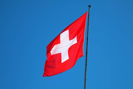 helvetica: Swiss flag agains blue sky
