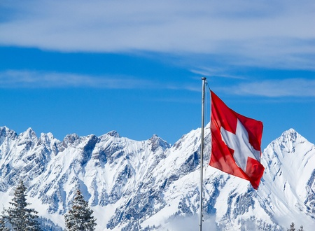 Swiss flag against snowy mountains
