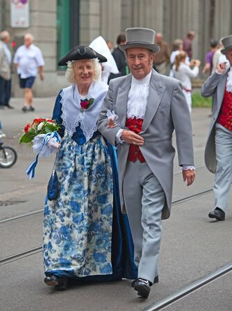 national costume: ZURICH - AUGUST 1: Couple in a traditional costumes of 19th century taking part in the Swiss National Day parade on August 1, 2009 in Zurich, Switzerland.