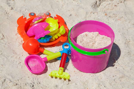 Bright plastic toys on a sandy beach photo