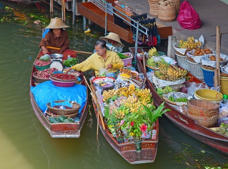 RATCHABURI, THAILAND - FEB 20: A woman buying chilli pepper for Thai food at Damnoen Saduak floating market on February 20, 2011 in Ratchaburi, Thailand. The loacal market is popular for traditional style food and old Thai culture.