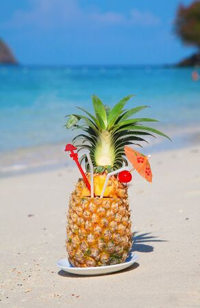 Pineapple cocktail on the white sandy beach photo