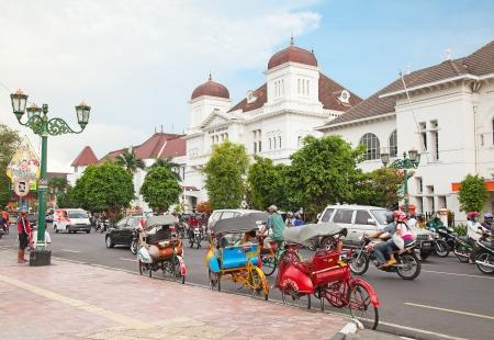 indonesia culture: YOGYAKARTA, INDONESIA - AUGUST 3: Rush hour on tghe main street of Yogyakarta with its typical hundreds of motorbikes, rickshaw and cars on August 3, 2010 in Yogyakarta, Indonesia.