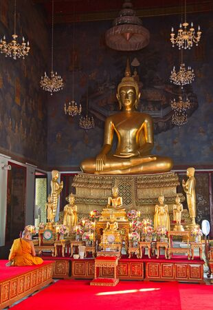 Buddhist monk praying in the temple photo