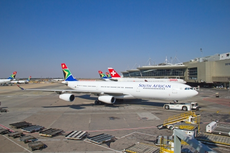 JOHANNESBURG - APRIL 18:Airbus A340 disembarking passengers after intercontinental flights on April 18, 2012 in Johannesburg, South Africa. Johannesburg Tambo airport is the busiest airport in Africa Stock Photo - 14340627