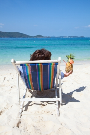 Woman relaxing with cocktail on the chair near the sea photo