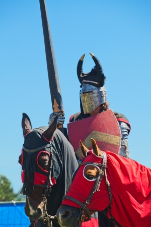 Knight in the historical costume on the horseback photo