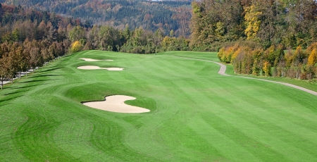 green grass of the golf course surrounded by autumnal forest Stock Photo