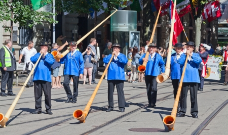 ZURICH - AUGUST 1: Swiss National Day parade on August 1, 2012 in Zurich, Switzerland. Musicians with alphorns playing traditional music. Stock Photo - 15986136
