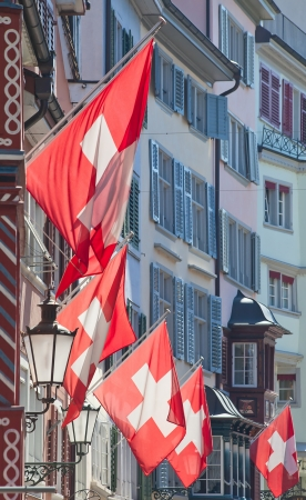 helvetica: Ancient street Augustinergasse in Zurich decorated with swiss flags