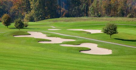 17021870: green grass of the golf course surrounded by autumnal forest Stock Photo
