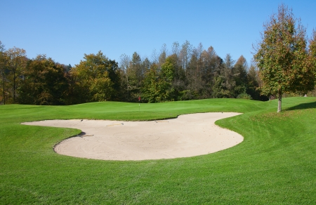 recreational area: green grass of the golf course surrounded by autumnal forest Stock Photo