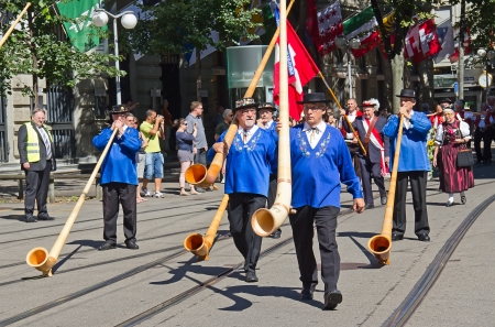 alphorn: ZURICH - AUGUST 1: Swiss National Day parade on August 1, 2009 in Zurich, Switzerland. Musicians with traditional alphorns in a historical costumes of cantone Uri.