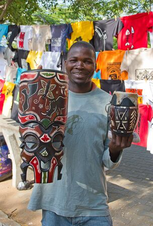 MAPUTO, MOZAMBIQUE – APRIL 29: Unidentified man selling traditional african masks on the market in Maputo, Mozambique on April 29, 2012. The local market is popular amoung locals and is one of the tourists attraction of the city.