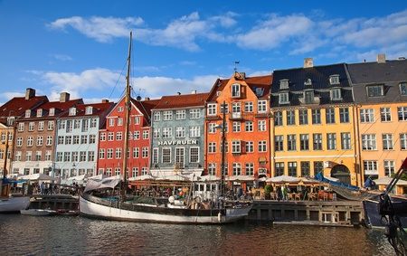 COPENHAGEN, DENMARK - AUGUST 25: unidentified people enjoying sunny weather in open cafees of the famous Nyhavn promenade on August 25, 2010 in Copenhagen, Denmark. Nyhavn district is one of the most famous landmark of Copenhagen.