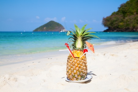 Fresh fruit cocktail on a tropical island beach photo