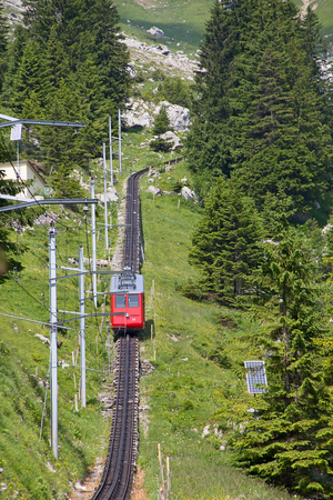 Swiss alpine cog railway train climbing up to the mountain photo