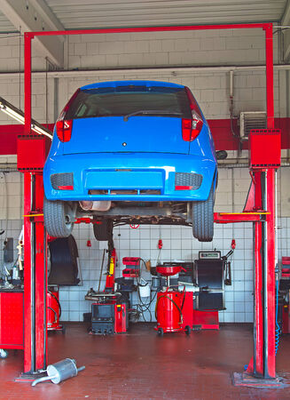 reparations: Car lifted up on the repair stand in garage