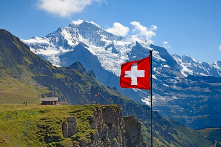 Swiss flag on the top of Mannlichen (Jungfrau region, Bern, Switzerland) Фото со стока