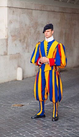 VATICAN CITY, VATICAN - AUGUST 1: Famous Swiss Guard surveil basilica entrance on August 1, 2014 in Vatican. The Papal Guard with 110 men is the worlds smallest army.