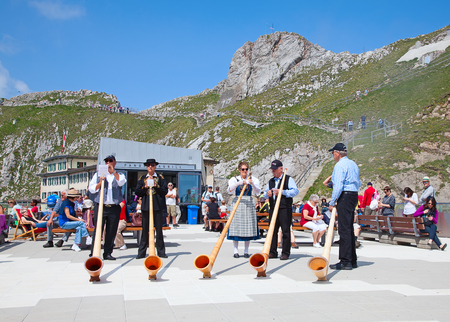 alphorn: MOUNT PILATUS - JULY 13: Unidentified people preparing traditional swiss alphorns for performance on July 13, 2013 on the top of Pilatus, Switzerland. Alphorn is traditional music instrument of Switzerland. Editorial