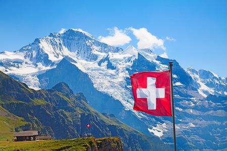 맨리 헨 (Männlichen) (융프라우 지역, 베른, 스위스)의 상단에 스위스 국기 스톡 콘텐츠