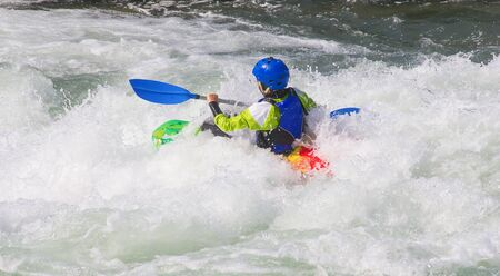 Female kayaker in the white water of tghe river