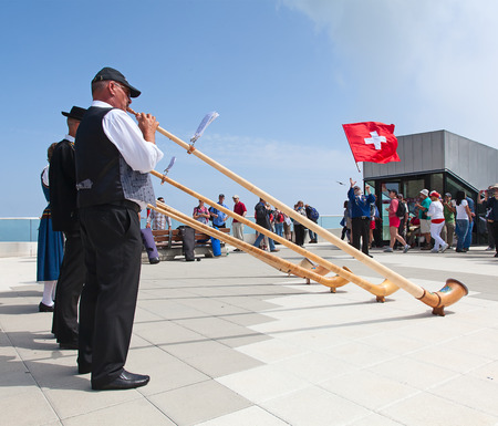 alphorn: MOUNT PILATUS - JULY 13: Unidentified people playing traditional swiss music with alphorns on July 13, 2013 on the top of Pilatus, Switzerland. Alphorn is traditional music instrument of Switzerland.