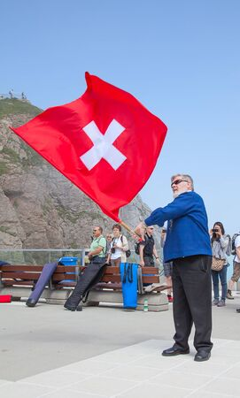 resonate: MOUNT PILATUS - JULY 13: Unidentified man demonstrating traditional swiss flag throwing on July 13, 2013 on the top of Pilatus, Switzerland. Flag twirling is one of the oldest swiss national sports.
