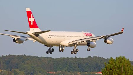 long haul journey: ZURICH - JULY 18: Swiss A-340 landing in Zurich airport after intercontinental flight on July 18, 2015 in Zurich, Switzerland. Zurich airport is home port for Swiss Air and one of the biggest european hubs.