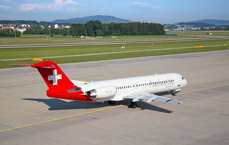 long haul journey: ZURICH - JULY 18: Fokker100 Helvetic airways taxing in Zurich after short haul flight on July 18, 2015 in Zurich, Switzerland. Helvetic airways is leading swiss discont airlines.