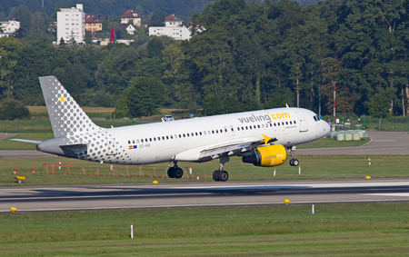 haul: ZURICH - JULY 18: Airbus A-320 Vueling landing in Zurich after short haul flight on July 18, 2015 in Zurich, Switzerland. Zurich airport is home for Swiss Air and one of biggest european hubs.