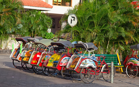 jogjakarta: YOGYAKARTA - AUGUST 03: Traditional rikshaw transport on streets of Yogyakarta, Java, Indonesia on August 03, 2010. Bicycle rikshaw remains popular means of transport in many Indonesian cities.